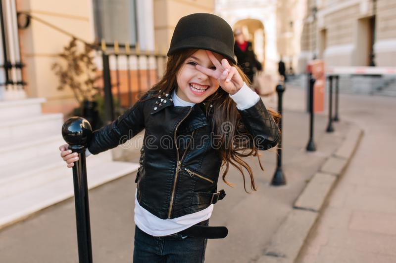 Excited little girl wearing leather jacket and belt holding iron pillar and posing with peace sign on city background royalty free stock photography