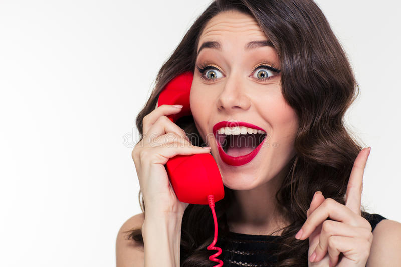 Excited lovely cute woman in retro style talking on telephone stock photo