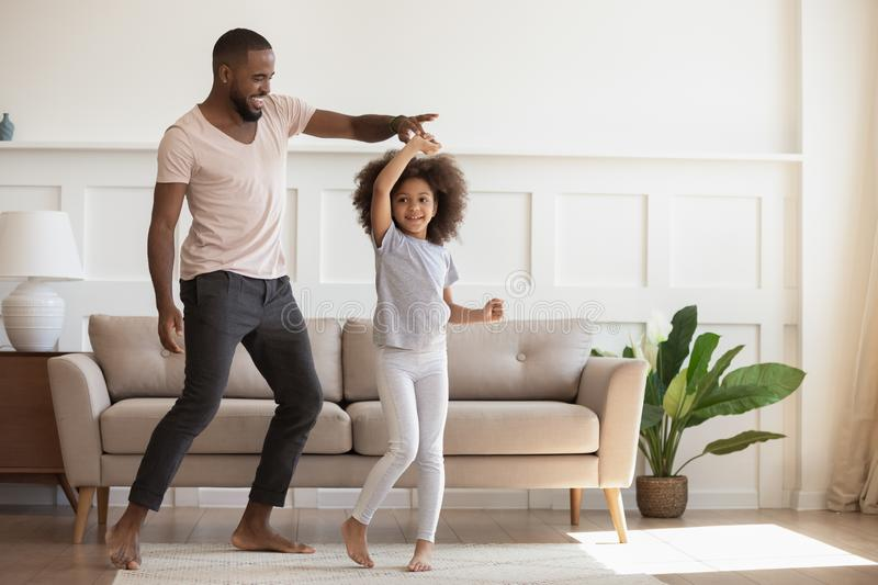 Excited loving african american smiling father twisting cute little daughter. stock photos
