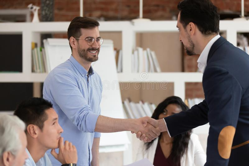 Smiling colleagues handshake greeting at office meeting. Excited male businesspeople handshake congratulate with promotion success at company office meeting stock photo