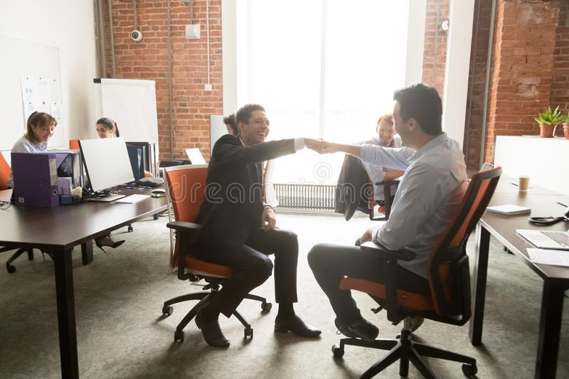 Excited male colleagues give fists bump in office stock image