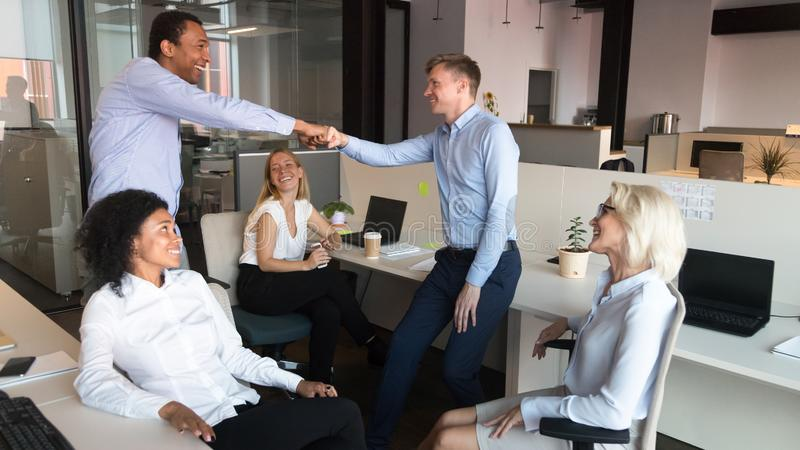 Excited male employees fist bump celebrating shared success. Excited diverse male employees give fist bump greeting at informal office meeting with colleagues stock photos