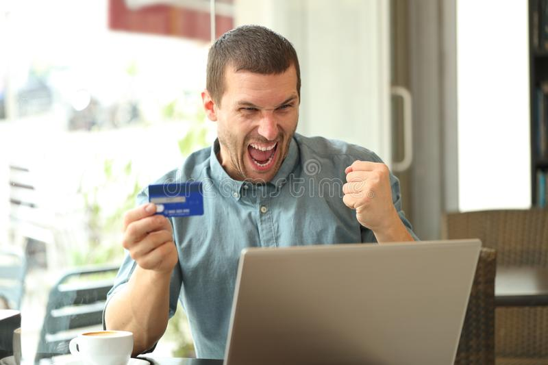 Excited man buying online with credit card and laptop. Sitting in a coffee shop stock image