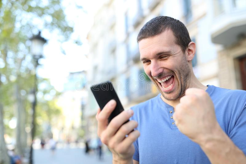 Excited man celebrating good news checking phone. Excited man celebrating good news checking mobile phone content standing in the street stock image