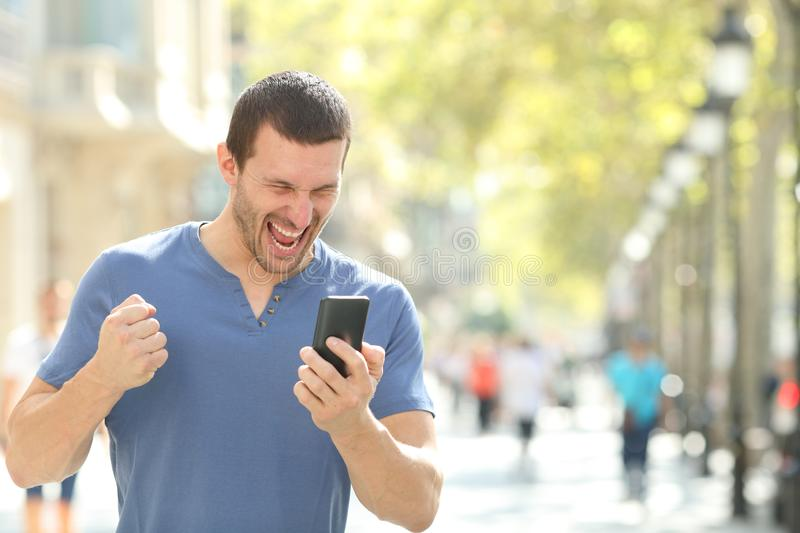 Excited man checking good news on mobile phone. Celebrating success in the street stock photo