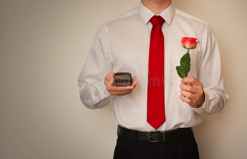 Excited man in dress shirt and red tie, holding a wedding ring box. Man holding a pink rose, proposing with a wedding ring. Formal wear stock photos