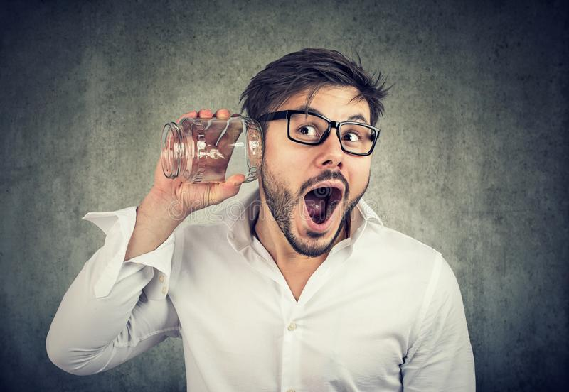 Excited man eavesdropping with glass jar. Adult bearded man in glasses looking super amazed while listening to rumors with glass jar on gray background royalty free stock image