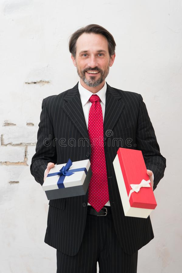 Excited man in elegant suit standing with two gift boxes. Presents for a girlfriend. Charismatic bearded man wearing elegant suit and keeping two pleasant gifts royalty free stock images