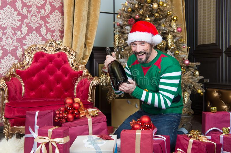 Excited man in elf costume smiling and holding big bottle royalty free stock photography
