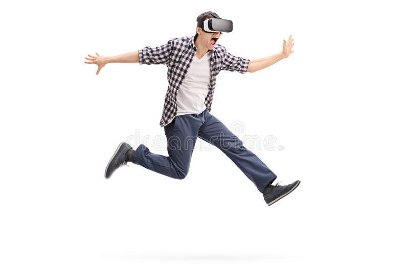 Excited man experiencing virtual reality. Excited young man experiencing virtual reality through a VR headset shot in mid-air isolated on white background royalty free stock image