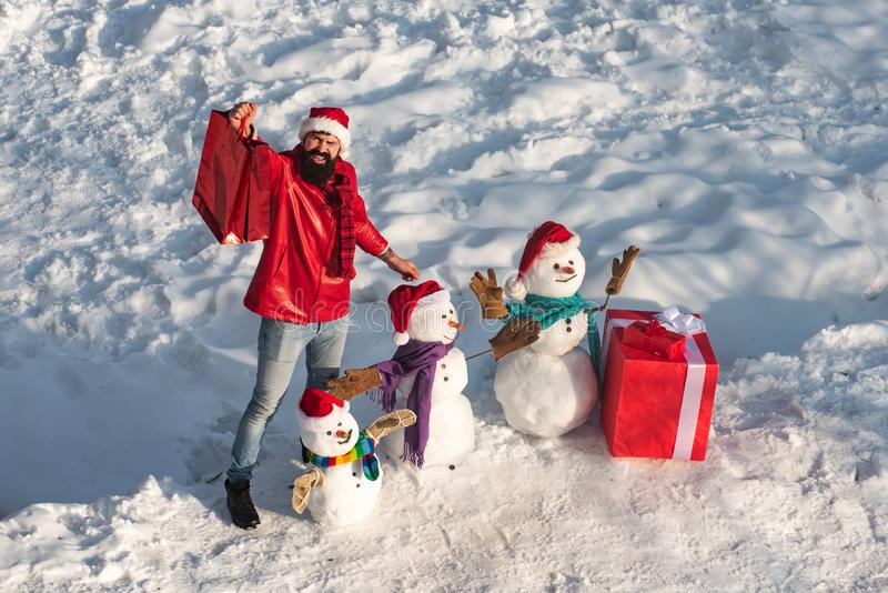 Excited man with funny snowman in stylish hat and scarf on snowy field. Happy winter snowman family with gift. Mother stock photos