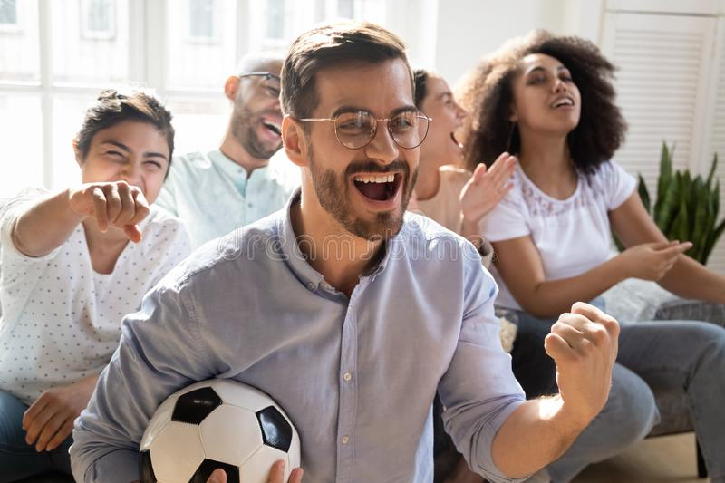 Excited man celebrating goal, watching football with diverse friends stock images