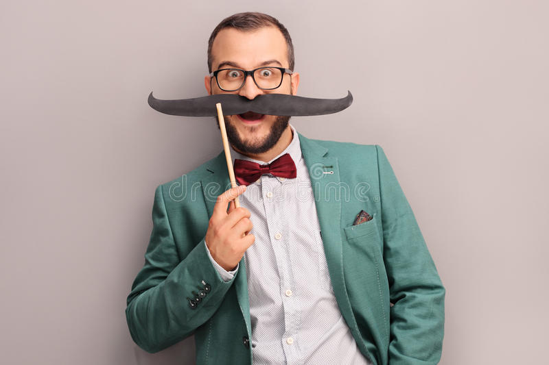 Excited man holding a fake mustache on his face royalty free stock photography