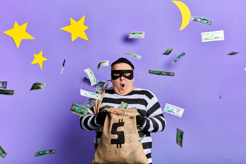 Excited man holding a money bag and surprised at flying paper money stock image