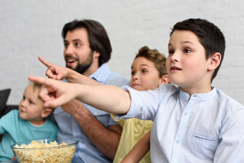 excited man and little sons with popcorn pointing away while watching film together stock image
