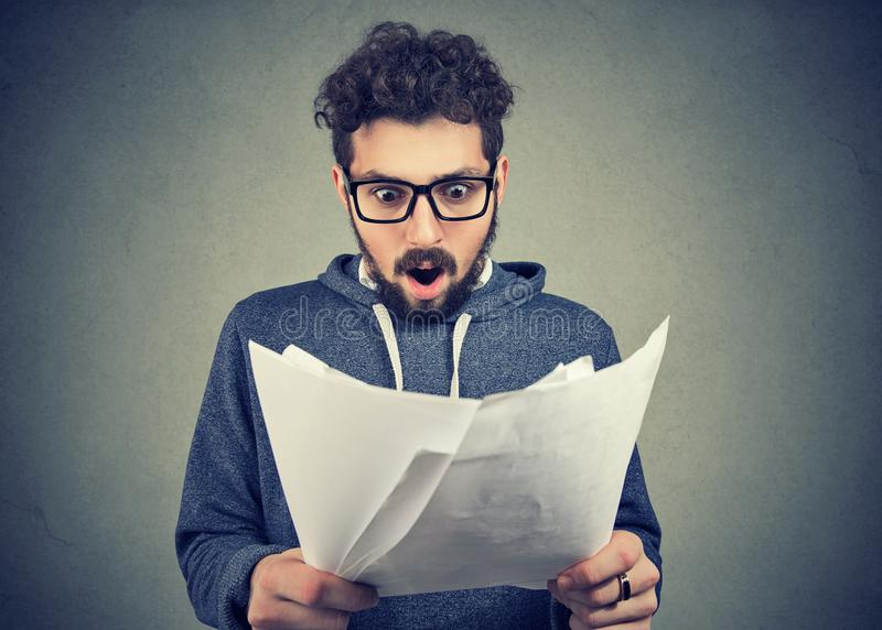 Excited man looking at papers in shock stock images