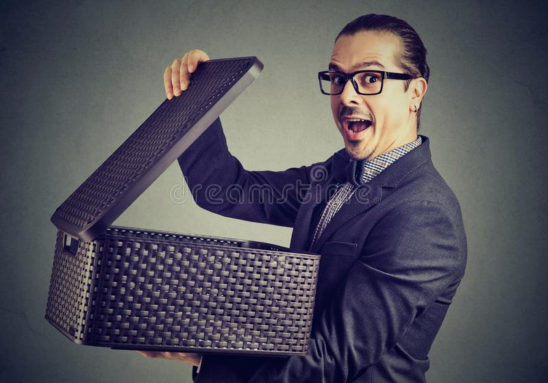 Excited man opening box with surprise. Amazed business man in suit and glasses opening box with secret and looking excitedly at camera on gray background stock photo