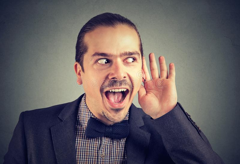 Excited man paying attention to rumors stock photography
