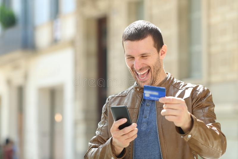 Excited man paying with credit card and phone. Excited man paying on line with credit card and mobile phone in the street stock photography