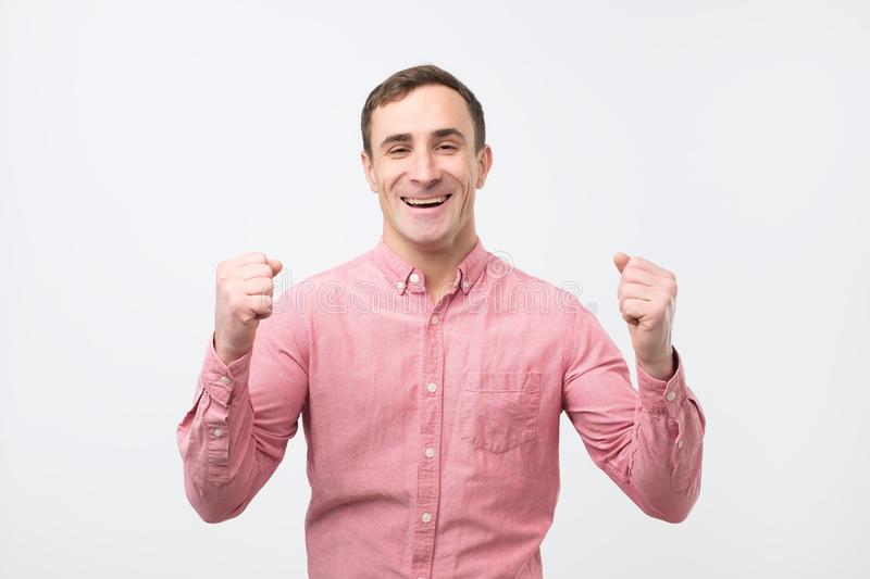 Excited man in pink shirt standing with fists up on white background. stock image