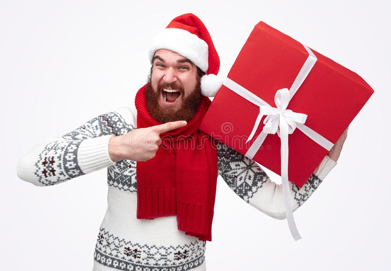 Excited man pointing at Christmas present royalty free stock images