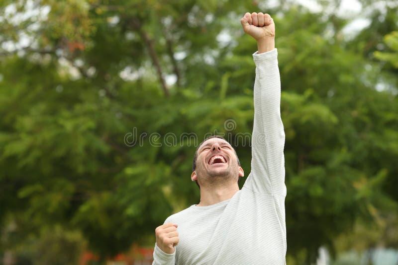 Excited man raising arm celebrating success in a park. Excited happy casual man raising arm celebrating success alone in a park royalty free stock images
