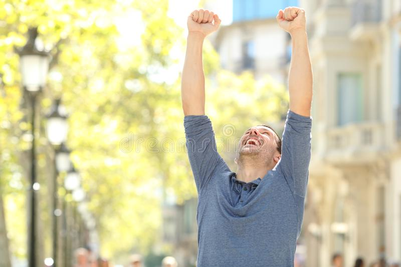Excited man raising arms celebrating success in the street. Of a big city stock images