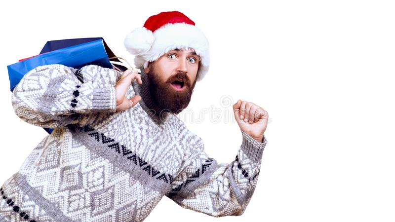 Excited man ready for Christmas Sale. Bearded man dressed in winter sweater and christmas hat. Winter sales. Shopper man running royalty free stock images