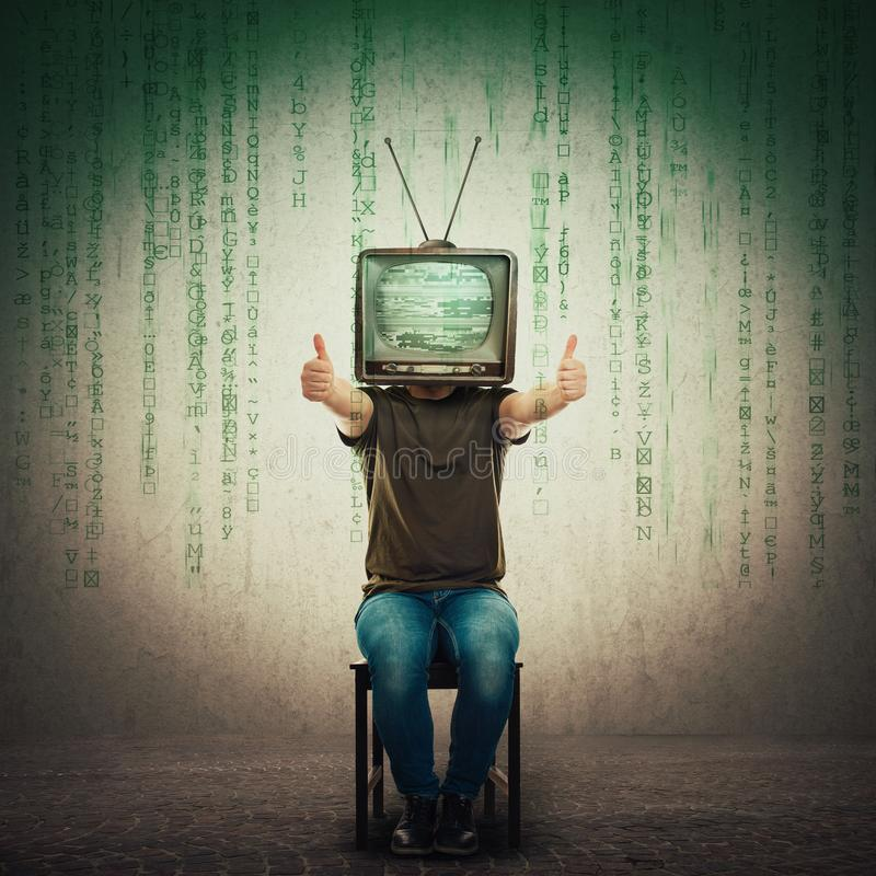 Excited man seated on a chair with an old TV instead of head showing thumbs up, positive feedback like gesture royalty free stock image