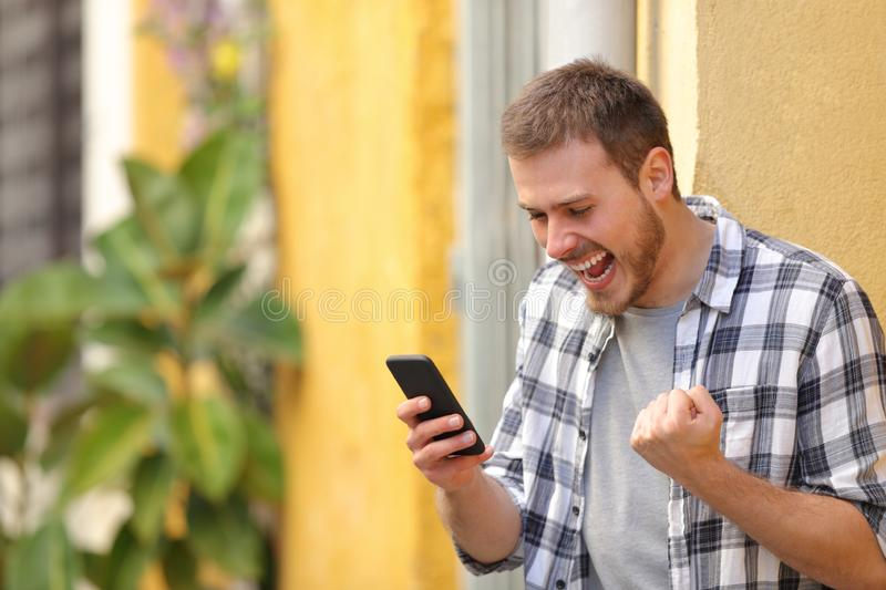 Excited man in the street checking smart phone. Celebrating good news royalty free stock photo