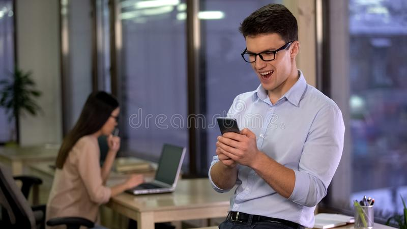 Excited man using smartphone application in office, modern technology, gadget. Excited men using smartphone application in office, modern technology, gadget royalty free stock images