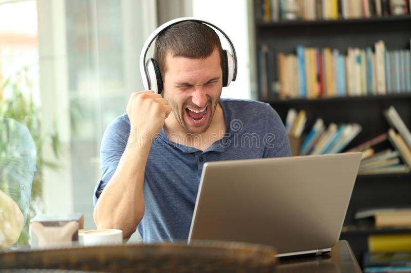 Excited man wearing headphones checking laptop. Celebrating good news sitting in a coffee shop royalty free stock images
