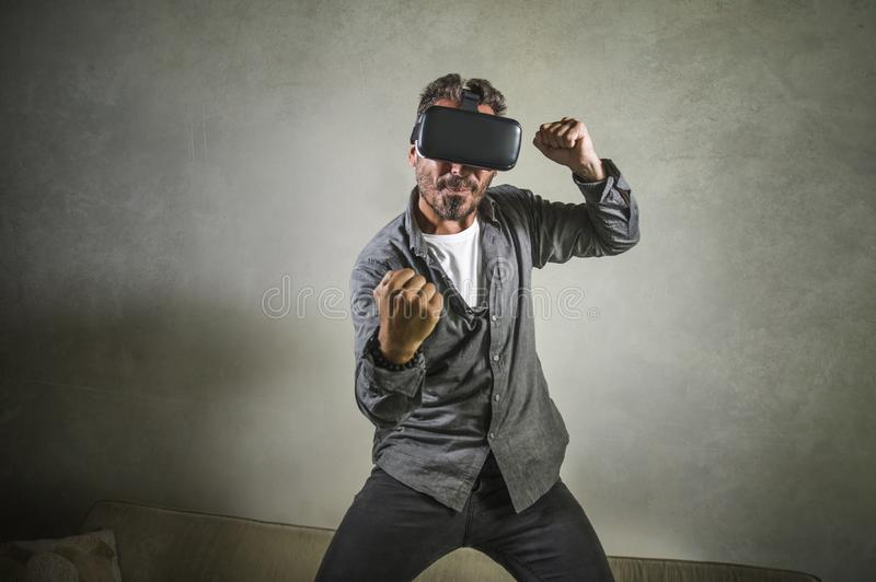 Excited man wearing virtual reality VR goggles headset experimenting 3d illusion playing fight or boxing video game enjoying. Young happy and excited man wearing royalty free stock photography