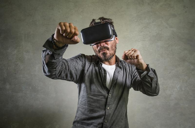 Excited man wearing virtual reality VR goggles headset experimenting 3d illusion playing fight or boxing video game enjoying. Young happy and excited man wearing royalty free stock images