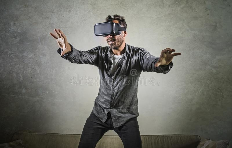 Excited man wearing virtual reality VR goggles headset experimenting 3d illusion playing video game touching illusion surprised at. Young happy and excited man royalty free stock photos