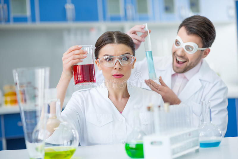 Excited man and woman scientists in protective glasses working with reagents stock photos