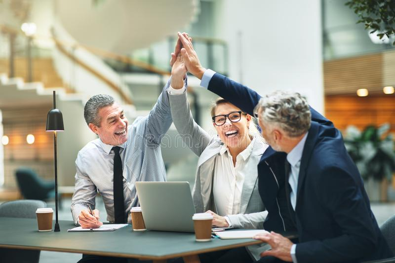 Excited mature businesspeople high fiving together in a modern o royalty free stock photo
