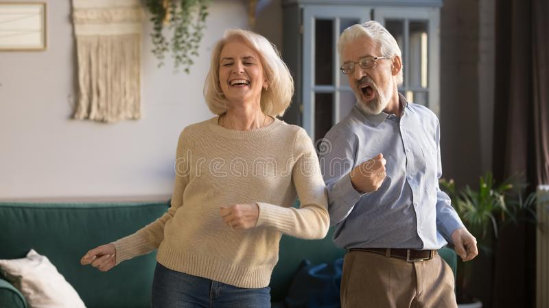 Excited mature couple, man and woman having fun, dancing together. Excited mature couple, laughing grey haired men and women having fun, dancing to favorite royalty free stock images