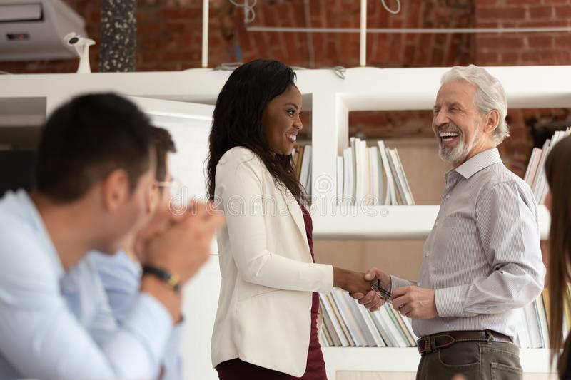 Smiling multiracial businesspeople handshake greeting at meeting. Excited mature male employee and african American female coworker handshake greeting at company stock images