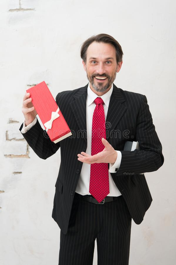 Excited mature man in classic suit holding elegant gift box stock photos