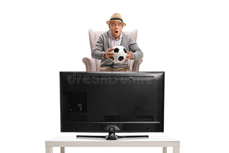 Excited mature man seated in an armchair watching soccer on television stock photos