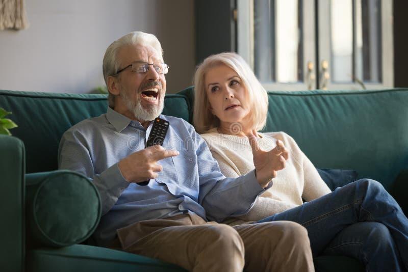 Annoyed elder woman looking at cheering senior husband, watching TV. royalty free stock photography