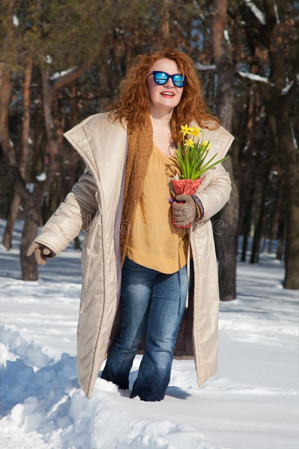 Excited mature woman walking through snowy forest royalty free stock images