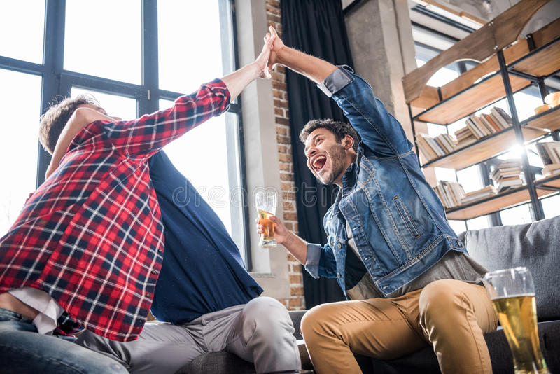 Excited men giving highfive. Excited young men giving highfive. young people having fun concept stock images