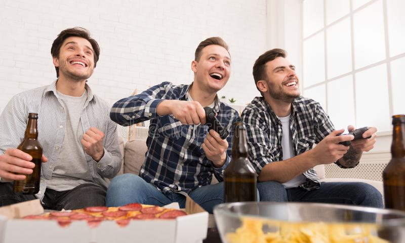 Excited men playing video game, having home party. And drinking beer stock photo