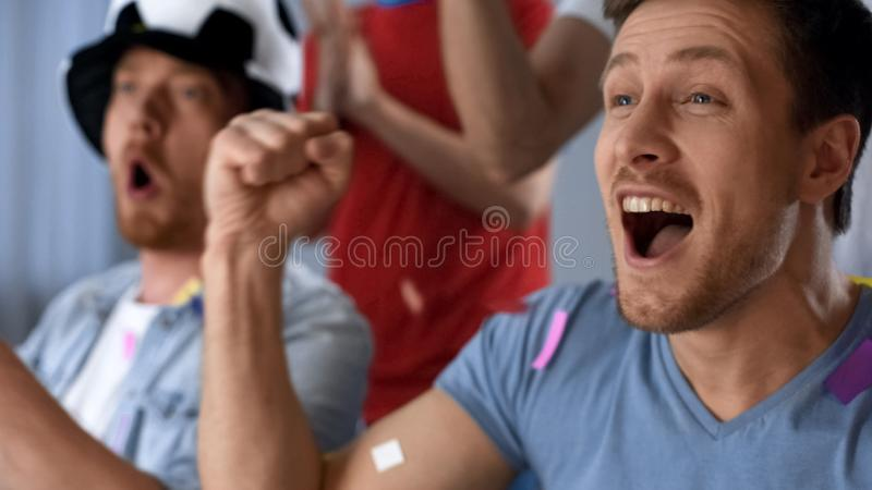 Excited men watching football game together, wearing fan horn, celebrating goal. Stock photo royalty free stock image