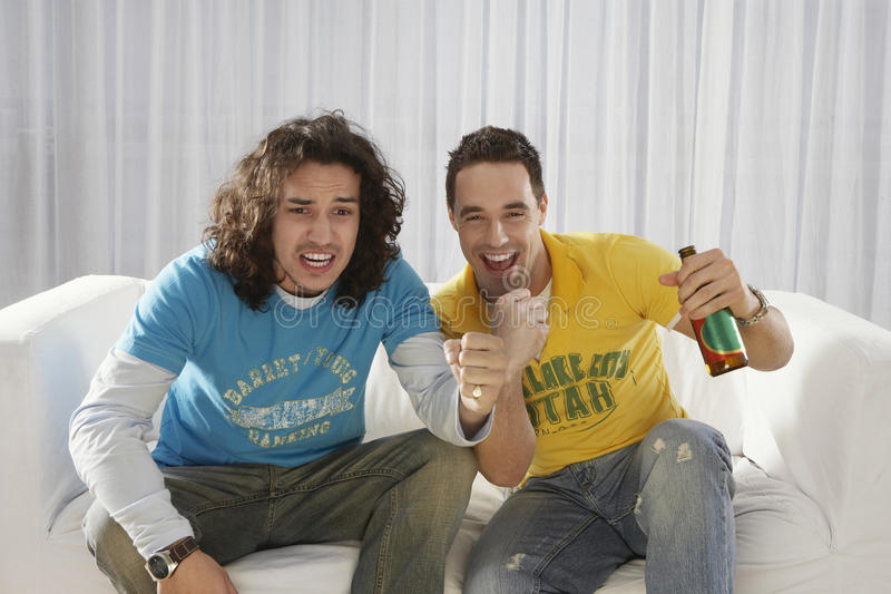 Excited Men Watching Television With Beer Bottle stock photos