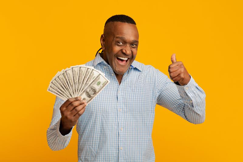Excited middle aged afro man showing thumb up with lots of money royalty free stock photos