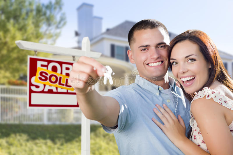 Excited Military Couple In Front of Home, House Keys and Sign. Mixed Race Excited Military Couple In Front of New Home with New House Keys and Sold Real Estate stock photography