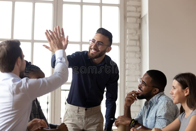 Smiling multiethnic male colleagues celebrate shared success stock photos